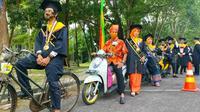 Seorang mahasiswa Universitas Lancang Kuning memakai sepeda ontel untu wisuda drive thru. (Liputan6.com/M Syukur)