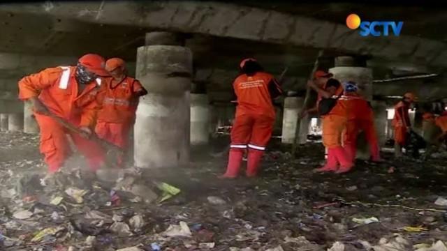 Lautan sampah di kolong Tol Wiyoto Wiyono ditargetkan bersih dalam waktu satu bulan. Petugas kembali berjibaku dengan sampah, guna melanjutkan upaya pembersihan.