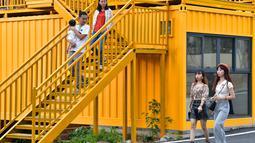 Para wisatawan muda terlihat di rumah berwarna-warni yang terbuat dari kontainer kargo di Desa Beilian yang berada di Xiyang, Kota Meizhou, Provinsi Guangdong, China selatan (24/11/2020). (Xinhua/Li He)