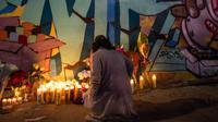 Seorang perempuan meletakkan lilin di depan mural bergambar Kobe Bryant dan putrinya Gianna Bryant di Los Angeles, Senin (27/1/2020). Pemain basket legendaris NBA Kobe Bryant bersama putrinya, Gianna yang berusia 13 tahun meninggal dunia dalam kecelakaan helikopter pada Senin (27/1). (Apu GOMES/AFP)