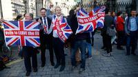 """Pendukung Brexit mengibarkan bendera Inggris setelah melihat hasil penghitungan sementara referendum Inggris yang menunjukkan mayoritas rakyat Inggris memilih """"Brexit"""" alias keluar dari Uni Eropa, di London, Kamis (23/6). (REUTERS/Neil Hall)"""