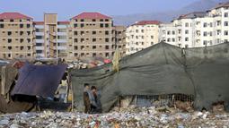 Dua anak laki-laki berjalan di dekat rumah darurat mereka di pinggiran Kabul, Afghanistan (27/11/2019). Puluhan ribu warga Afghanistan yang terlantar secara internal tinggal di kamp-kamp, yang kekurangan fasilitas dasar, di Afghanistan. (AP Photo / Tamana Sarwary)