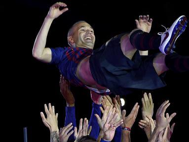Gelandang Barcelona, Andres Iniesta, diangkat rekan-rekannya usai melawan Real Sociedad pada laga La Liga Spanyol di Stadion Camp Nou, Barcelona, Minggu (20/5/2018). Dirinya berpisah dengan klub yang 22 tahun telah dibela. (AFP/Lluis Gene)