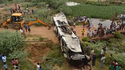 Warga dan polisi menyaksikan bus tingkat yang rusak usai mengalami kecelakaan di jalan bebas hambatan di Agra, India, Senin (8/7/2019). Sopir diduga mengantuk sehingga bus tersebut menabrak pembatas jalan Tol Yamuna dan terjun ke sungai di bawahnya. (Pawan Sharma/AFP)