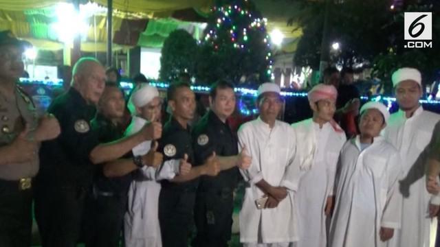 Puluhan anggota jemaah tabligh menjaga misa natal di Gereja Katedral Medan. Dengan pakaian khasnya mereka menarik perhatian masyarat.