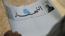 Seorang pria memegang surat kabar terkemuka Lebanon, An-Nahar, dengan halaman kosong tanpa berita di Beirut, Kamis (11/10). Surat kabar kosong itu sebagai protes atas situasi politik negeri yang tak kunjung membentuk pemerintahan baru. (AFP/JOSEPH EID)