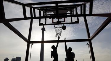 Dua orang warga berusaha memasukan bola saat olahraga basket di Kawasan Monumen Nasional, Jakarta, Rabu (13/2). Monas merupakan salah satu lokasi yang kerap dijadikan ruang olahraga bagi warga ibukota. (Bola.com/M. Iqbal Ichsan)