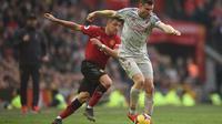 Duel Alexis Sanchez dan James Milner pada laga lanjutan Premier League yang berlangsung di stadion Old Trafford, Manchester, Minggu (24/2). Man United bermain imbang 0-0 kontra Liverpool. (AFP/Oli Scarff)