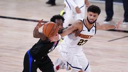 Pebasket Denver Nuggets, Jamal Murray, berebut bola dengan pebasket Los Angeles Clippers, Patrick Beverley pada gim ketujuh semifinal playoff NBA di Lake Buena Vista, Selasa (15/9/2020).  Nuggets menang dengan skor 104-89. (AP/Mark J. Terrill)