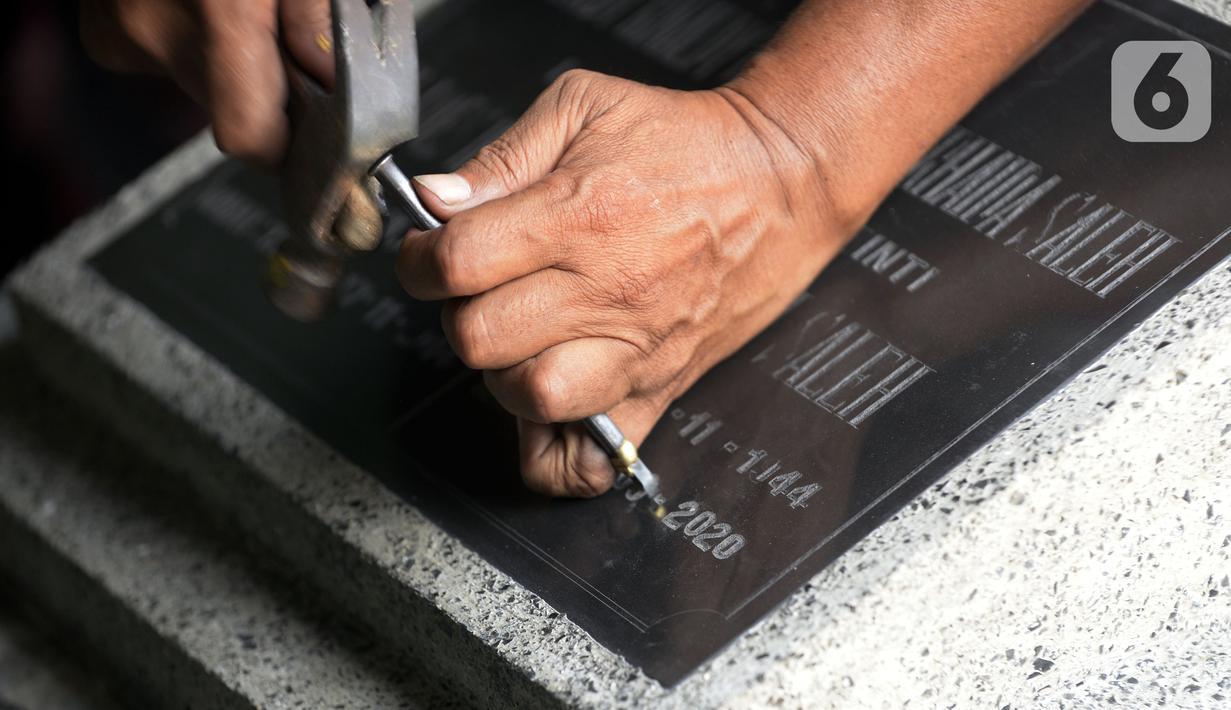 Yadi (50) mengukir batu nisan pesanan pembeli di Parakan, Pamulang, Tangerang Selatan, Banten, Jumat (18/9/2020). Kasus positif Covid-19 di Indonesia bertambah 3.891 menjadi 236.519 orang, sementara 170.774 orang dinyatakan sembuh, dan 9.336 orang meninggal dunia. (merdeka.com/Dwi Narwoko)