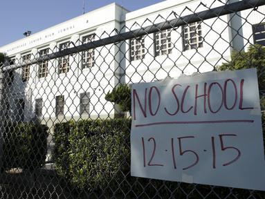 Sebuah kertas berisi pemberitahuan libur terpasang di Florence Nightingale Middle School, Los Angeles, Selasa (15/12). Seluruh sekolah di Los Angeles, ditutup selama satu hari pada Selasa (15/12), karena adanya ancaman teror bom. (REUTERS/Jason Redmond)