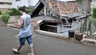 Pejalan kaki melintasi sebuah rumah usang di halaman belakang apartemen Thamrin Executive Residence, Kebon Melati, Jakarta, Minggu (22/9/2019). Rumah milik Elis (46) itu menjadi satu-satunya yang bertahan di antara gedung-gedung tinggi yang dibangun sejak 2012 silam. (merdeka.com/Iqbal S Nugroho)