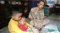 Pasangan suami istri Iwan (37) dan Kesih (35) bersama tiga orang anaknya, Kevin  Setiawan (16) ,Yuda Setiawan (12) dan  Yuska Setiawan (2,5 ) hidup di bawah garis kemiskinan. (Liputan6.com/Abramena)