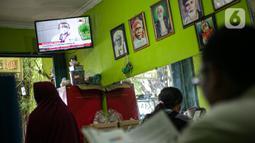 Warga menonton televisi yang menayangkan penyuntikan vaksin COVID-19 terhadap Presiden Joko Widodo atau Jokowi di Jakarta, Rabu (13/1/2021). Vaksin Sinovac yang disuntikkan terhadap Jokowi sudah mendapatkan izin terbit dari BPOM. (Liputan6.com/Faizal Fanani)