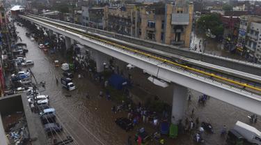 Sejumlah warga beraktivitas di bawah jembatan komuter line yang banjir setelah hujan lebat di Lahore (16/7/2019). Di Kashmir yang dikelola Pakistan, para pejabat pemerintah mengatakan sedikitnya 23 orang tewas setelah hujan lebat memicu banjir bandang. (AFP Photo/Arif Ali)