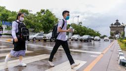 Sejumlah siswa yang mengenakan masker menyeberangi jalan saat pulang sekolah di Vientiane, Laos, Selasa (19/5/2020). Pemerintah Laos telah mengumumkan bahwa semua siswa di negara itu dapat kembali bersekolah mulai 2 Juni mendatang. (Xinhua/Kaikeo Saiyasane)
