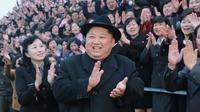 Pemimpin Korea Utara Kim Jong-Un tersenyum sambil bertepuk tangan saat mengunjungi Universitas Guru Pyongyang yang baru direnovasi di Pyongyang (17/1). (KCNA VIA KNS/AFP)