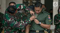 KSAD Jenderal TNI Andika Perkasa (kiri) memasangkan nama baru Aprilio Perkasa Manganang kepada Aprilia Manganang di Mabes AD, Jakarta, Jumat (19/3/2021). PN Tondano resmi mengabulkan permohonan pengubahan nama Aprilia Manganang menjadi Aprilio Perkasa Manganang. (Liputan6.com/Faizal Fanani)