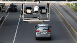 Kendaraan melintas di bawah rambu sistem jalan berbayar atau electronic road pricing ( ERP) di Jalan Merdeka Barat, Jakarta, Kamis (14/2). Meskipun rambu telah dipasang, penerapan ERP hingga saat ini masih terus dikaji. (Liputan6.com/Immanuel Antonius)