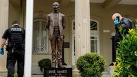 Lubang-lubang peluru terlihat di kolom di belakang patung pahlawan kemerdekaan Kuba Jose Marti ketika petugas Dinas Rahasia AS menyelidiki, setelah polisi mengatakan seseorang dengan senapan serbu menembaki Kedutaan Besar Kuba di Amerika Serikat. [Andrew Harnik / AP]