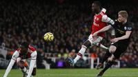 Gelandang Arsenal, Nicolas Pepe, berebut bola dengan gelandang Manchester City, Kevin De Bruyne, pada laga Premier League di Stadion Emirates, London, Minggu (15/12). Arsenal kalah 0-3 dari City. (AFP/Ian Kington)