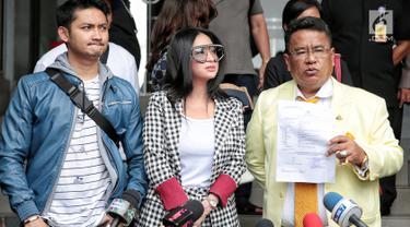 Pedangdut Dewi Perssik (tengah) ditemani suami, Angga Wijaya (kiri) dan kuasa hukumnya Hotman Paris Hutapea mendatangi Polda Metro Jaya, Jakarta, Senin (5/11). Kedatangan Dewi untuk melaporkan keponakannya, Rosa Meldianti. (Liputan6.com/Faizal Fanani)