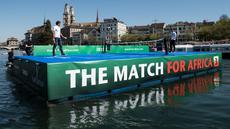 Petenis asal Swiss, Roger Federer (kiri) bertanding melawan petenis asal Inggris, Andy Murray di lapangan kecil di atas sungai Kota Zurich, Senin (10/4). Kedua petenis itu terlibat dalam program amal The Match For Africa 3. (Ennio Leanza/Keystone via AP)