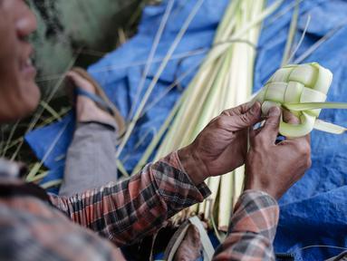Pedagang sedang menganyam kulit ketupat di Pasar Palmerah, Jakarta, Rabu (2/6). Jelang lebaran penjualan kulit ketupat mulai ramai, omsetnya melonjak hingga 10 kali lipat. (Liputan6.com/Faizal Fanai)