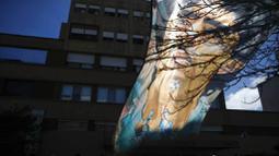 Bendera bergambar Diego Maradona berkibar di depan Rumah Sakit di La Plata, Argentina, Selasa (3/11/2020). Sejumlah fans Argentina berkumpul di depan rumah sakit untuk memberi dukungan kepada sang legenda. (AP/Natacha Pisarenko)
