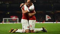 Selebrasi Aubameyang dan Sokratis Papastathopoulus pada leg 2, babak 16 besar Liga Europa yang berlangsung di stadion Emirates, London, Jumat (22/2). Arsenal menang 3-0 atas Bate Borisov. (AFP/Glyn Kirk)