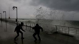 Dua pria menghindari ombak besar yang menghantam tembok di Beirut  (6/1). Badai kuat di Lebanon membawa suhu dingin dan salju ke pegunungan dan hujan lebat, angin kencang melanda pantai bagian dari negara Mediterania tersebut. (AP Photo/Bilal Hussein)