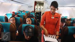 Pramugari membagikan cokelat kepada penumpang dalam penerbangan di Pesawat Garuda Indonesia menuju, Padang, Sumatera Barat, Jumat (21/4). Menyambut Hari Kartini, penerbangan Garuda Indonesia diawaki seluruhnya oleh perempuan. (Liputan6.com/Angga Yuniar)