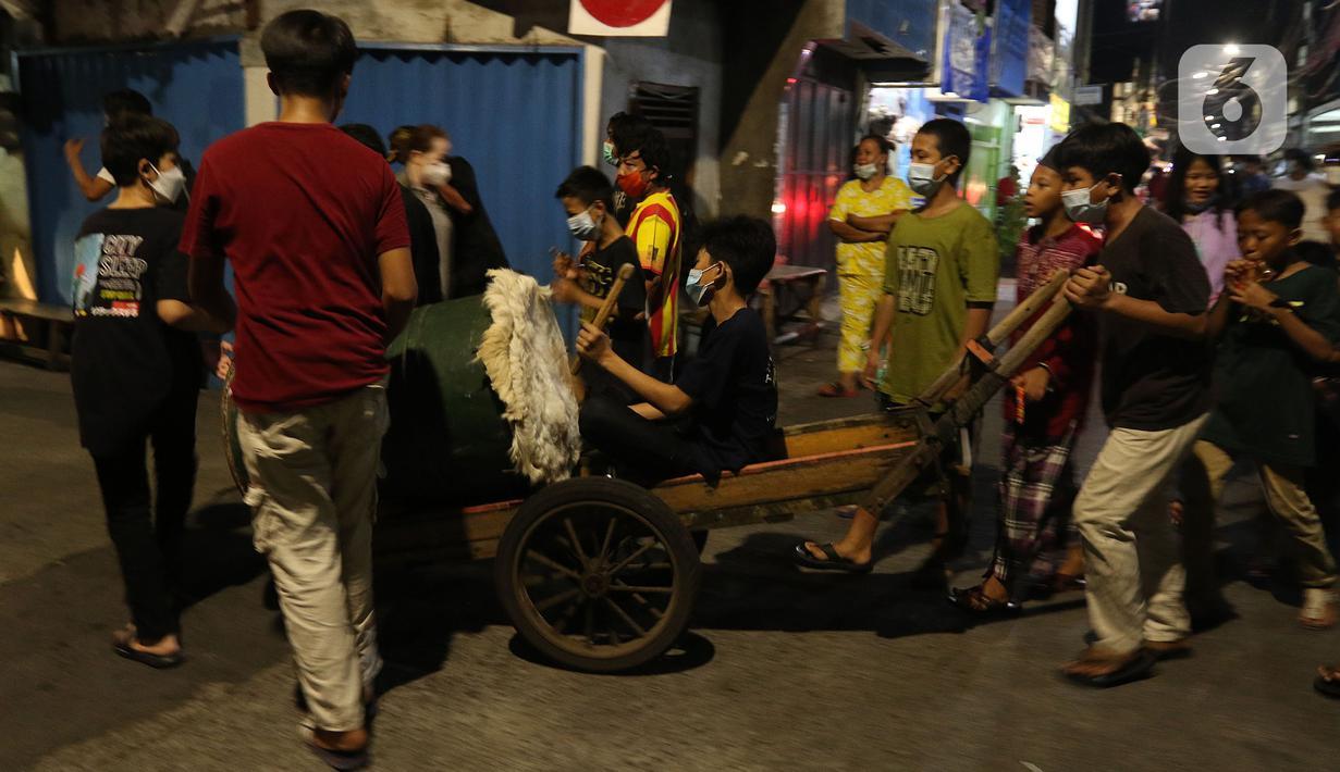 Warga menggelar takbiran keliling di kawasan Jalan Kartini, Sawah Besar, Jakarta, Rabu (12/5/2021) malam. Warga DKI Jakarta dilarang melakukan takbiran keliling pada malam Idul Fitri 1442 Hijriah. (Liputan6.com/Herman Zakharia)