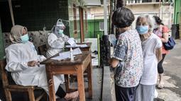 Warga lansia melakukan registrasi vaksinasi COVID-19 di SDN 05 Penggilingan, Jakarta, Kamis (25/2/2021). Pemerintah berharap vaksinasi tahap kedua terhadap lansia selesai pada Mei 2021 guna menekan penyebaran COVID-19. (merdeka.com/Iqbal S. Nugroho)