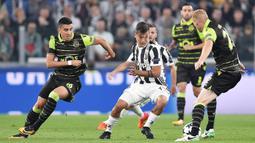 Striker Juventus, Paulo Dybala, berusaha melewati kepungan pemain Sporting Lisbon pada laga Liga Champions di Stadion Allianz, Turin, Rabu (18/10/2017). Juventus menang 2-1 atas Sporting. (AP/Alessandro Di Marco)