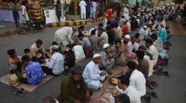 Muslim Pakistan berdoa sebelum berbuka puasa bersama di sepanjang jalan di Karachi pada 7 Mei 2019. Ketika bulan suci Ramadan mulai di Pakistan, banyak masyarakat muslim memanfaatkan buka puasa gratis yang disponsori oleh badan-badan amal dan orang-orang kaya. (RIZWAN TABASSUM / AFP)