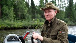 Presiden Rusia, Vladimir Putin mengendalikan sebuah kapal selama liburan mini di kawasan Siberia Tyva. Foto dirilis oleh biro pers Kremlin, pada 5 Agustus 2017. (Alexei Nikolsky / Sputnik, Foto Kolam Kremlin via AP)