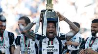 Bek Juventus, Dani Alves mengangkat trofi Liga Italia di Juventus Stadium, Turin, (21/5). Bagi Juveventus, ini merupakan scudetto ke-33 atau yang keenam secara beruntun. (AP Photo/Antonio Calanni)