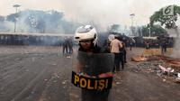 Polisi menghalau mahasiswa dalam demonstrasi menolak pengesahan RUU KUHP dan revisi UU KPK di depan Gedung DPR, Jakarta, Selasa (24/9/2019). Mahasiswa lari tunggang langgang setelah aparat kepolisian menembakkan gas air mata dan water cannon. (Liputan6.com/JohanTallo)