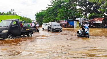 Warga mendorong sepeda motor karena mogok akibat nekat melintasi banjir di Pekanbaru.