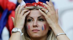Suporter wanita Prancis merapikan rambutnya sebelum menyaksikan pertandingan melawan Norwegia pada grup A Piala Dunia Wanita 2019 di Stadion Nice, Prancis (12/6/2019). (AP Photo/Claude Paris)