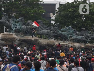 Massa aksi demo tolak omnibus law UU Cipta Kerja naik ke atas patung arjuna wiwaha mengibarkan bendera merah putih di Jalan Medan Merdeka Barat, Jakarta Pusat, Selasa (20/10/2020). Mereka sempat mengibarkan bendera selama kurang lebih lima menit di atas patung. (Liputan6.com/Herman Zakharia)