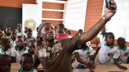 Didier Drogba melakukan foto selfie bersama anak-anak saat membuka sekolah dasar di Onahio, Pokou-Kouamekro, Pantai Gading, (20/1/2018).  Drogba menjadi salah satu sponsor utama untuk sekolah tersebut. (AFP/Sia Kambou)