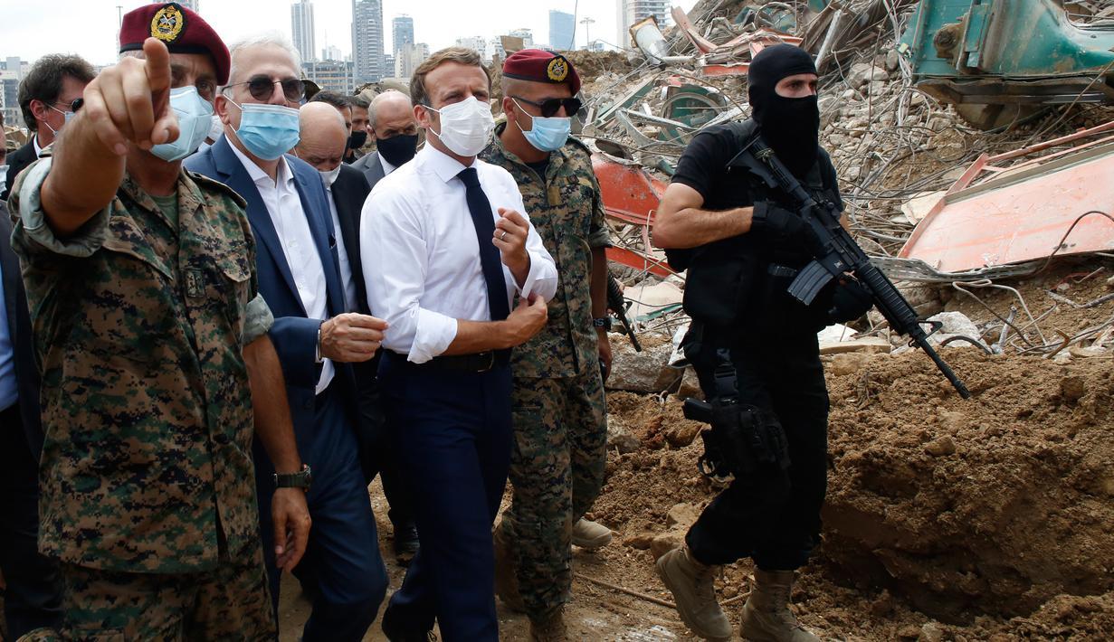 Presiden Prancis Emmanuel Macron (tengah) mengunjungi lokasi ledakan yang menghancurkan di pelabuhan Beirut, Lebanon, Kamis (6/8/2020). Presiden Macron tiba di Beirut untuk menawarkan bantuan Prancis ke Lebanon setelah ledakan besar yang meluluhlantakkan Kota Beirut. (AP Photo/Thibault Camus, Pool)