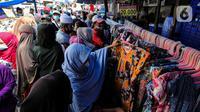 Pengunjung memilih pakaian yang dijual di Pasar Tanah Abang, Jakarta Pusat, Minggu (2/5/2021). Pusat Grosir Pasar Tanah Abang ramai didatangi pengunjung yang berbelanja menjelang Lebaran dengan berdesak-desakan tanpa jaga jarak. (Liputan6.com/Johan Tallo)