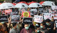 Pegawai KPK membawa poster saat menggelar aksi di Lobi Gedung KPK, Kuningan, Jakarta, Jumat (6/9/2019). Dalam aksi menolak revisi UU KPK tersebut, mereka mengenakan baju serba hitam lengkap dengan masker penutup mulut dan membawa payung. (merdeka.com/Dwi Narwoko)