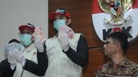 Petugas KPK menunjukkan barang bukti hasil operasi tangkap tangan terhadap Bupati Jombang, Nyono Suharli Wihandoko di Gedung KPK, Jakarta, Minggu (4/2). KPK menyita uang Rp 25,5 Juta dan 9.500 US Dollar. (Liputan6.com/Helmi Fithriansyah)