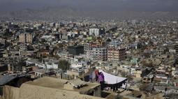 Seorang wanita menjemur pakaiannya di atap yang menghadap kota Kabul di Kabul, Afghanistan (28/11/2019). Puluhan ribu warga Afghanistan yang terlantar secara internal tinggal di kamp-kamp, yang kekurangan fasilitas dasar, di Afghanistan. (AP Photo/Altaf Qadri)