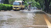 Pengendara melintasi genangan air di Jalan Raya Juanda Kota Depok, Sabtu (20/2/2021). (Liputan6.com/Dicky Agung Prihanto)