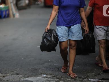 Warga membawa barang belanjaan dengan menggunakan kantong plastik di Kawasan Pasar Jatinegara, Jakarta, Selasa (30/6/2020). Pemerintah Provinsi DKI Jakarta bakal resmi menerapkan larangan penggunaan kantong plastik sekali pakai mulai Rabu, 1 Juli 2020 besok. (Liputan6.com/Faizal Fanani)